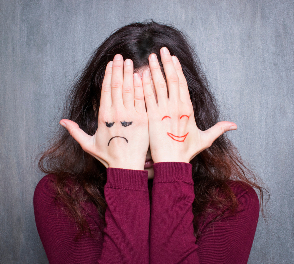 Woman with happy and sad faces on hands -- Type 1 Diabetes and Mood