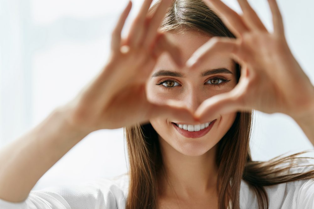 Woman making heart shape around eyes -- Diabetes Eye Problems